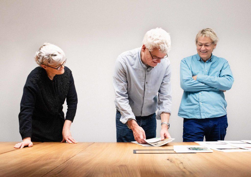 Bea Szenfeld, Mårten Carstenfors och Lars Lerin framför bilder på ett skrivbord.